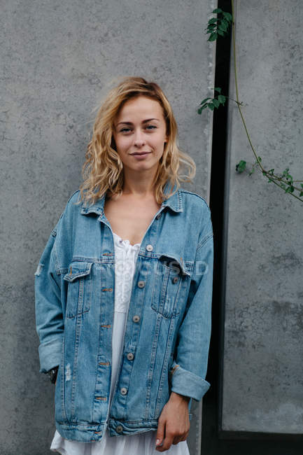 Young adult woman in casual clothing against gray wall looking at camera — Stock Photo