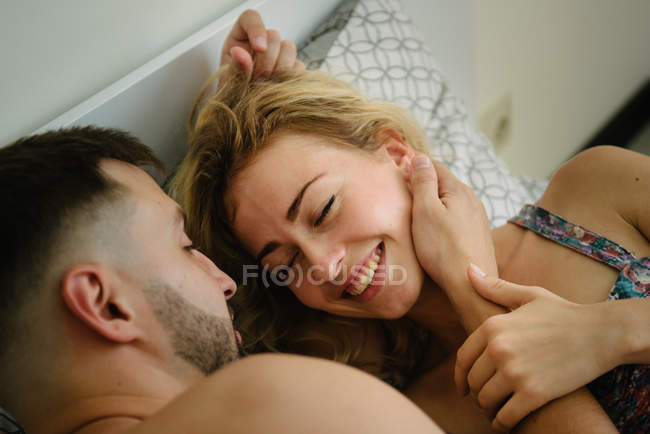 High angle view of young adult couple hugging on bed — Stock Photo