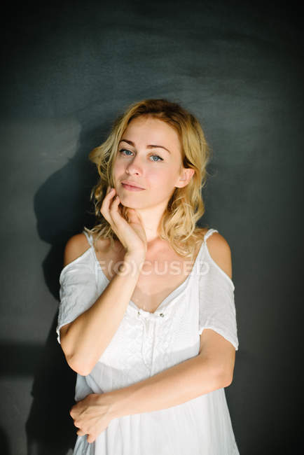 Portrait of woman in white dress against dark-gray background — Stock Photo