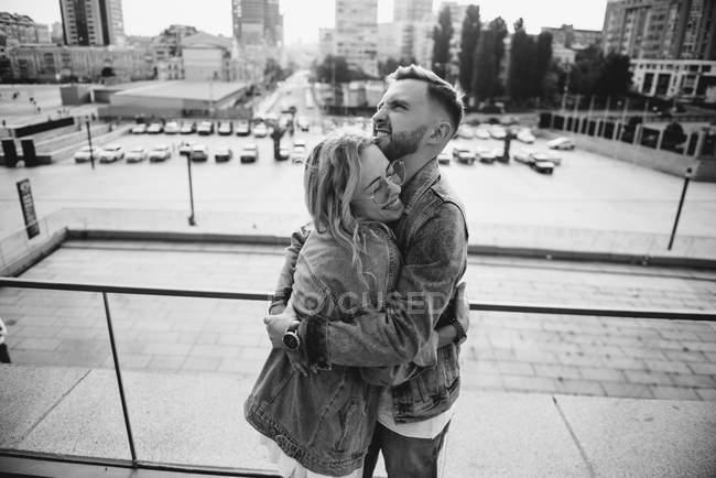Вид сбоку обнимающей молодой взрослой пары в повседневной одежде, черно-белая — стоковое фото