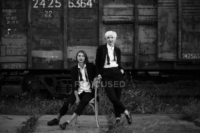Full length shot of two women posing at railway station, one sitting on the chair and other standing near — Stock Photo