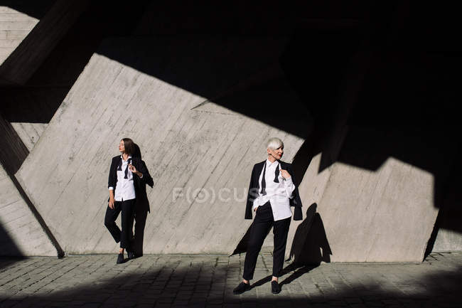 Full length shot of two women in classic suits posing against geometrical concrete wall outdoors — Stock Photo