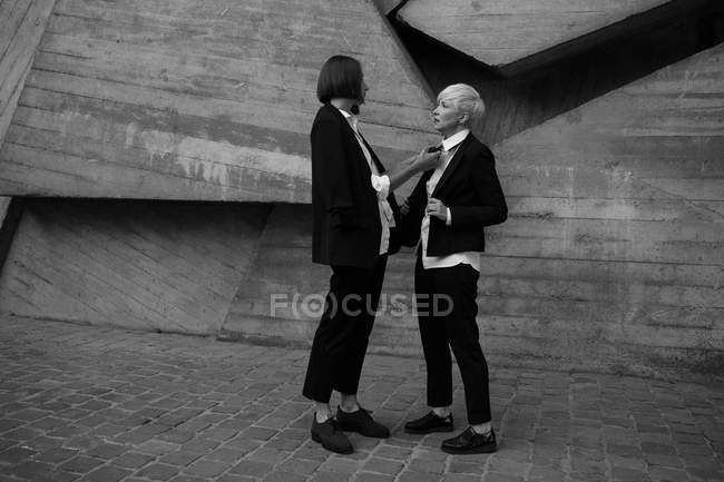 Full length shot of woman tying tie her friend against  geometrical concrete wall outdoors — Stock Photo