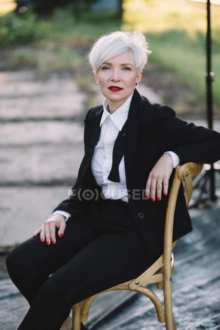 Портрет женщины в черном, сидящей на стуле возле железнодорожной станции — стоковое фото