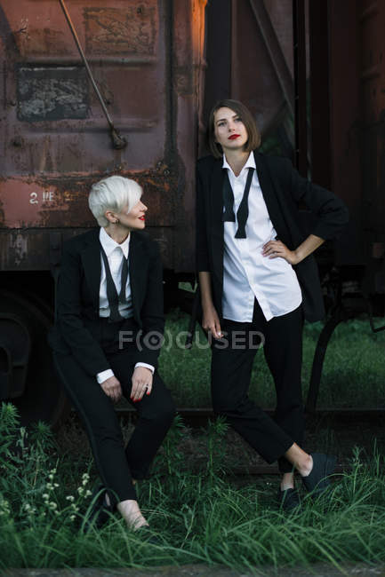 Full length shot of two women posing at railway station — Stock Photo
