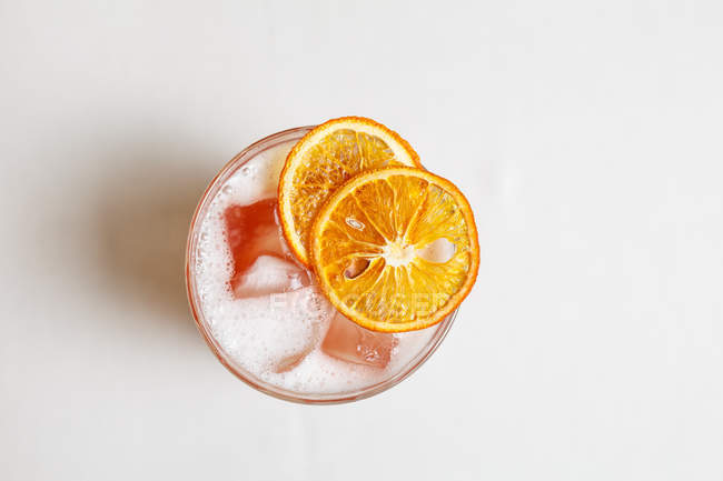 Top view of cold cocktail with ice cubes and dried orange slices — Stock Photo