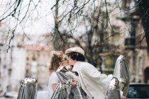 Fashionable couple kissing with silver balloons on street — Stock Photo