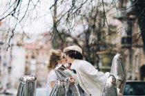 Modischer paar küssen mit silbernen Ballons auf Straße — Stockfoto