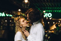 Young stylish couple leaning to kiss in bar interior — Stock Photo
