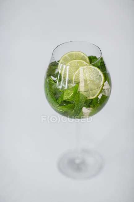 Closeup view of iced drink with mint leaves and lime slices in glass on white surface — Stock Photo