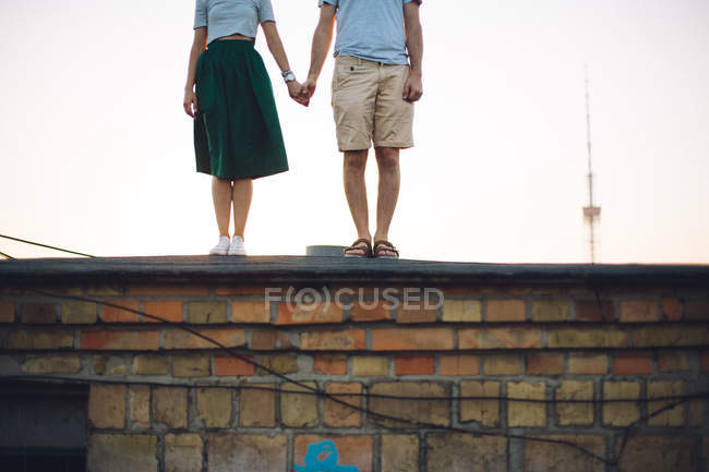 Cropped image of couple standing on roof and holding hands — Stock Photo