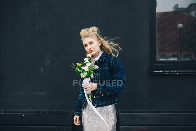 Young blonde woman in denim jacket holding bridal bouquet on street — Stock Photo