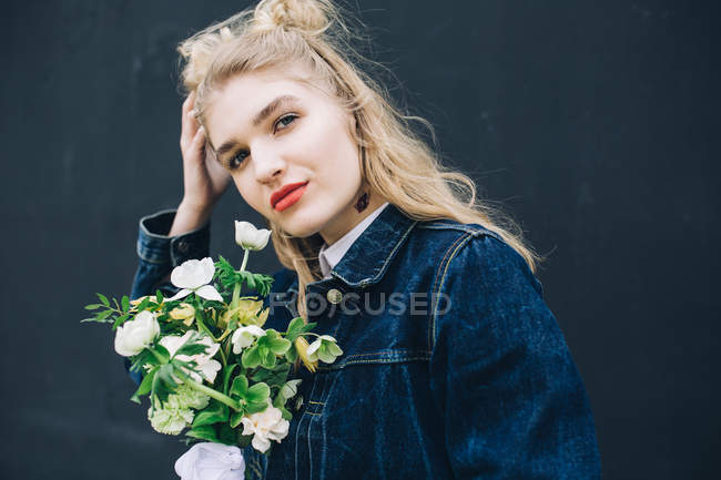 Portrait of young blonde woman in denim jacket holding bouquet — Stock Photo
