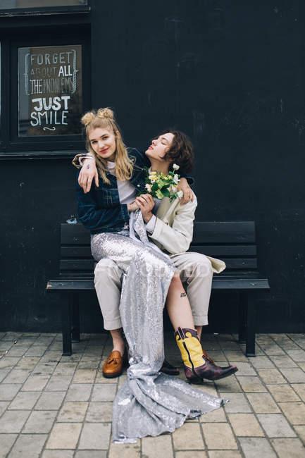 Mujer recién casada sentada en el regazo del novio en el banco urbano - foto de stock