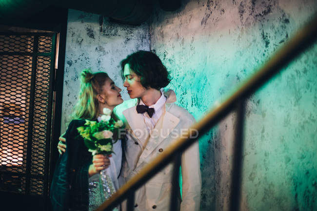 Newlywed couple embracing at staircase in grunge building — Stock Photo