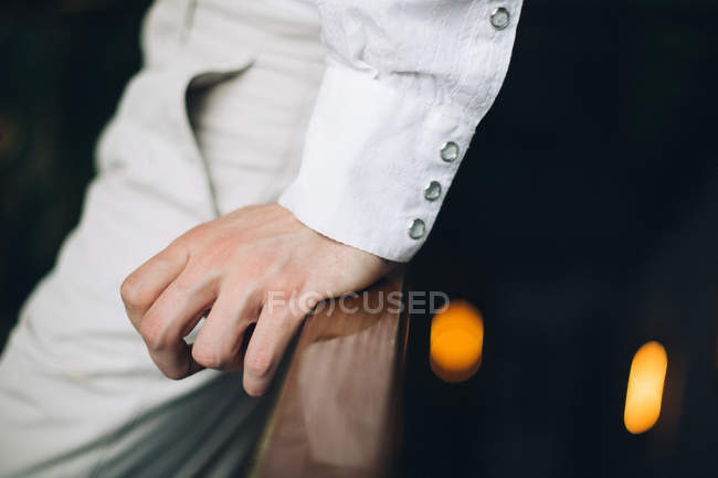 Крупным планом мужской руки с белой рубашки манжеты, опираясь на деревянные перила — стоковое фото