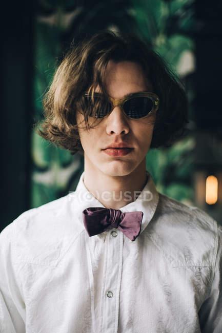 Портрет молодого человека с вьющимися волосами в солнцезащитные очки и галстук-бабочку — стоковое фото