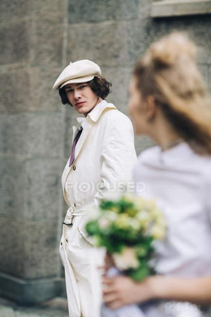 Человек серьезно молодоженов в газетчик шапочка с невестой на переднем плане — стоковое фото