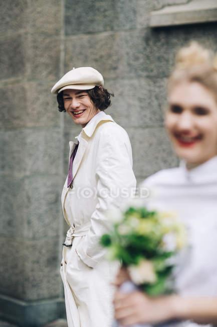 Новобрачная человек в газетчик шапочка, улыбаясь с невестой на переднем плане — стоковое фото