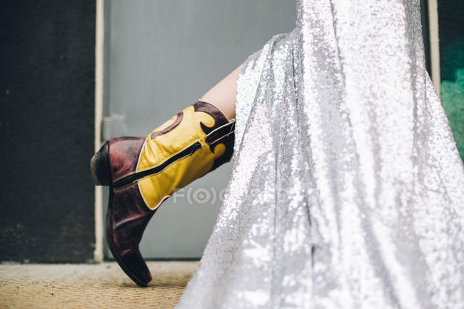 Cropped view of female leg with long silver skirt and cowgirl boot — Stock Photo