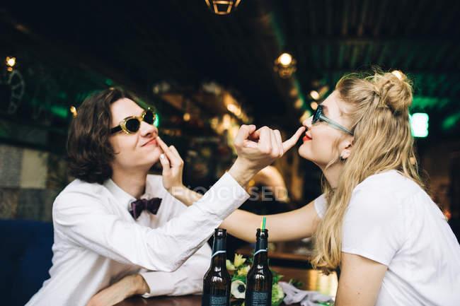 Jovem casal em óculos de sol tocar rostos e se divertindo bar interior — Fotografia de Stock