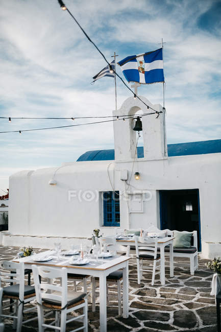 Scenic view of street cafe with church bell and cross, Paros, Aegean Sea, Cyclades, Greece — Stock Photo