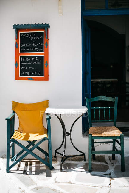 Closeup view of chairs and table under sign of street cafe — Stock Photo