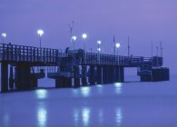 Pier over sea water at night — Stock Photo