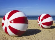 Red and white water balls on the beach — Stock Photo
