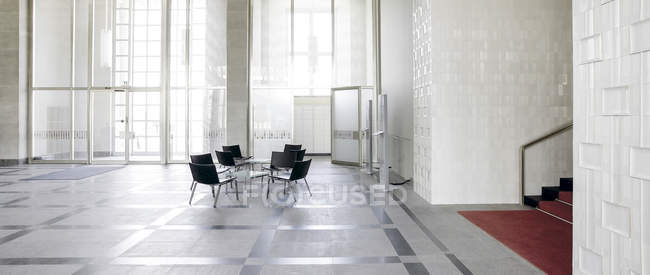 Mesa y sillas en el vestíbulo de un edificio de oficinas moderno - foto de stock
