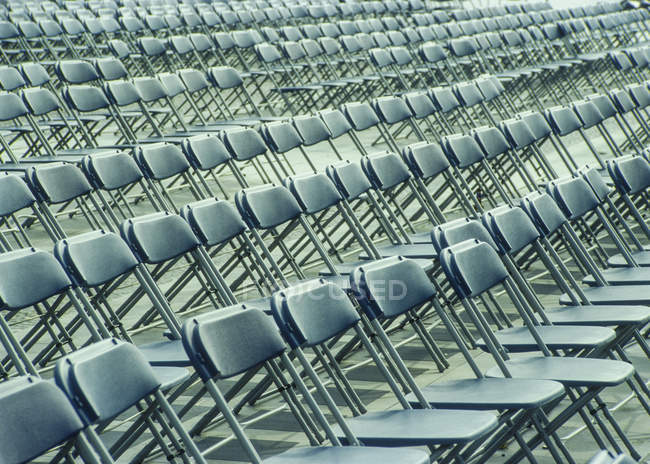 Rows of chairs made of folding chairs indoors u2014 Stock Photo & Rows of chairs made of folding chairs indoors u2014 Stock Photo | #187832796