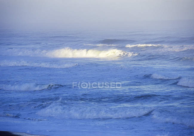 Surf waves, white spray, light on wave at sea — Stock Photo