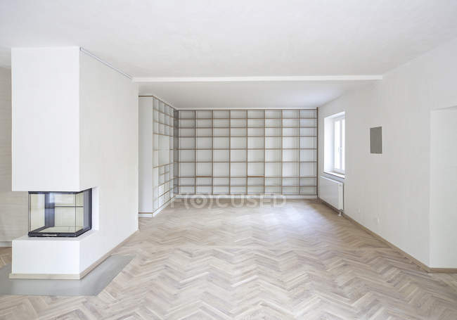 Empty white living room with parquet floor and shelf wall — Stock Photo