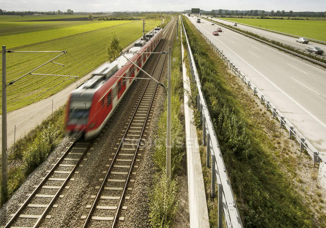 S-Bahn train next to highway, blurred motion — Stock Photo