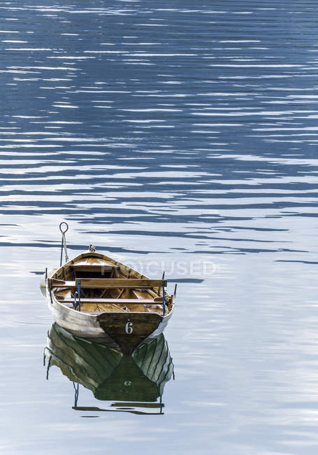 Wooden rowing boat floats in calm waters — Stock Photo