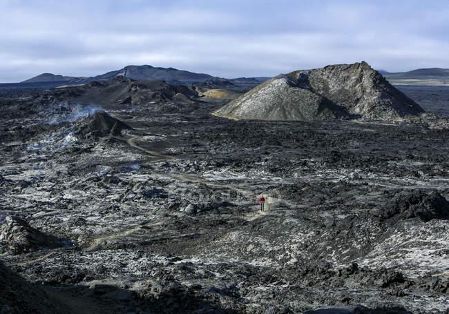 Islande, paysage volcanique noir, randonneur à pied sur un terrain — Photo de stock