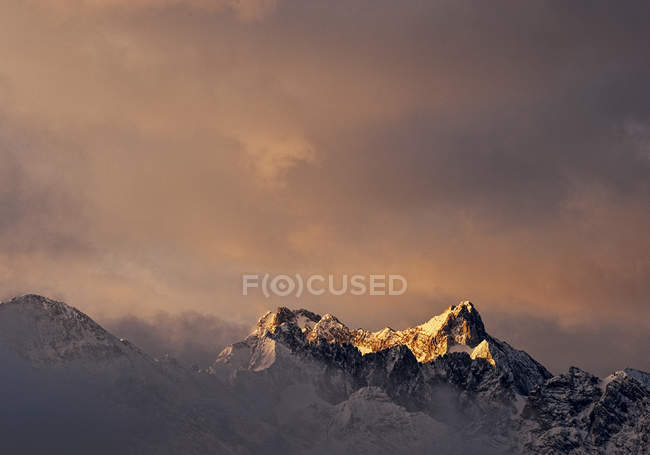 Mountain peak under stormy clouds at dawn, alps — Stock Photo