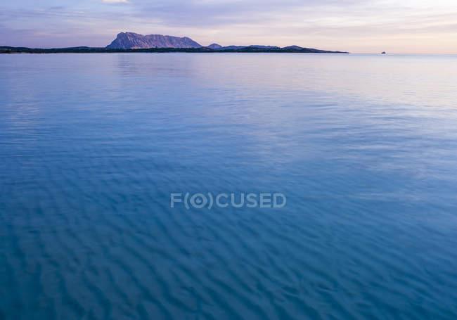 Спокійне блакитне море, гори на задньому плані — стокове фото