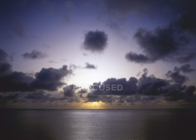Sunset at the sea water under cloudy sky — Stock Photo