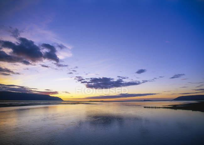 Atardecer en el mar bajo las nubes, Islandia - foto de stock