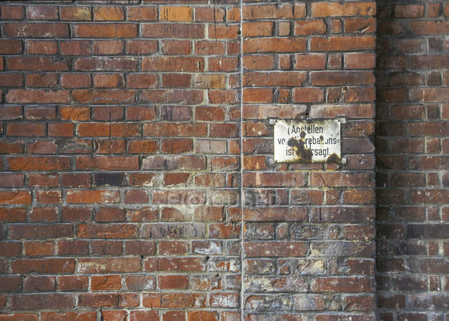 Old brick wall with sign outdoors — Stock Photo