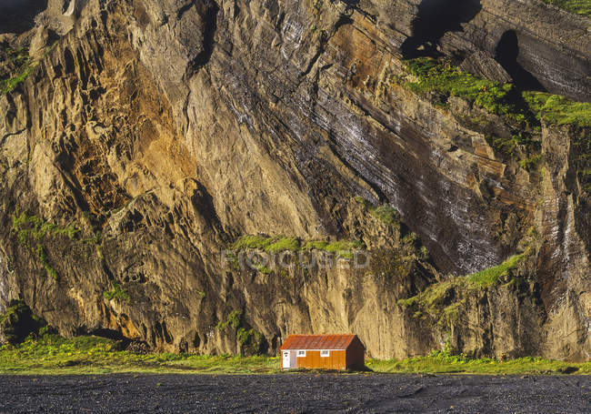 Small hut in front of a steep rock face, Iceland — Stock Photo