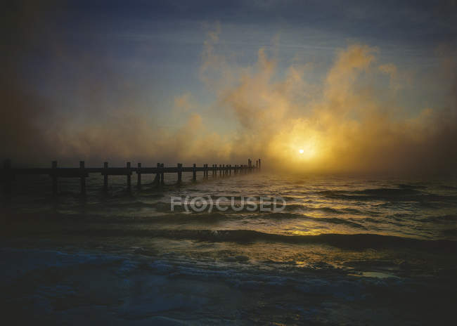 Sunset in the fog on wintry lake with footbridge — Stock Photo