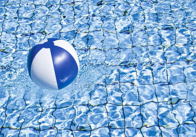 Bola de praia flutua na água da piscina — Fotografia de Stock