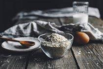 Ciotola di vetro di farina di grano saraceno sul tavolo in legno rustico — Foto stock