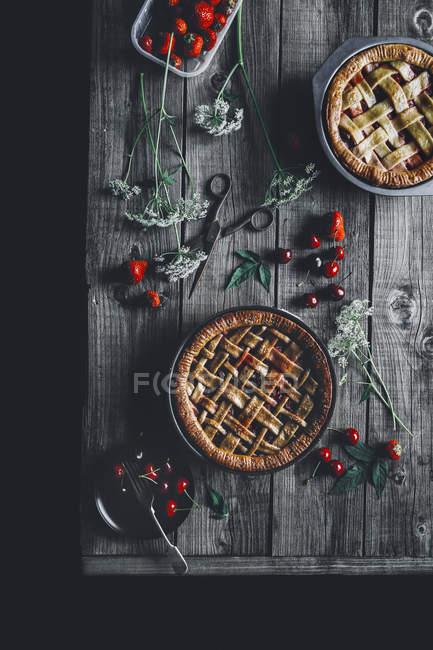 Torte vaniglia con ciliegie e fragole sulla tavola di legno — Foto stock