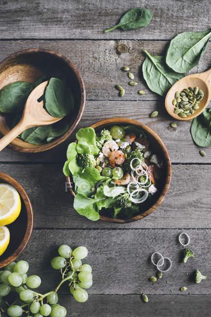 Салат миска с креветками, брокколи и зеленый виноград на деревянной поверхности — стоковое фото