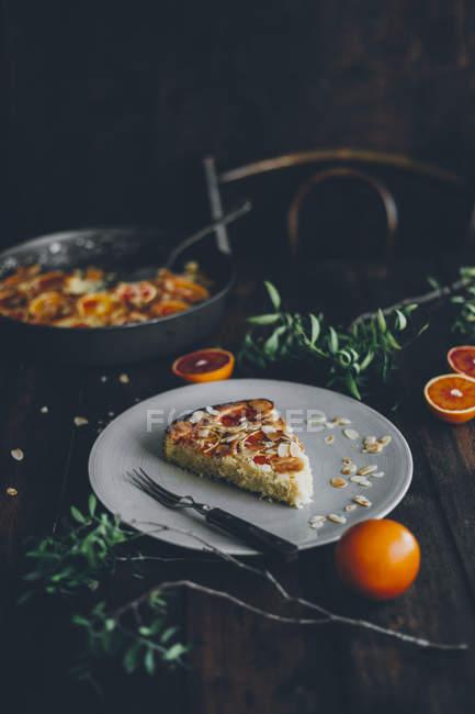 Parte della torta di agrumi di cardamomo fatti in casa sulla targhetta applicata sul legno scuro — Foto stock
