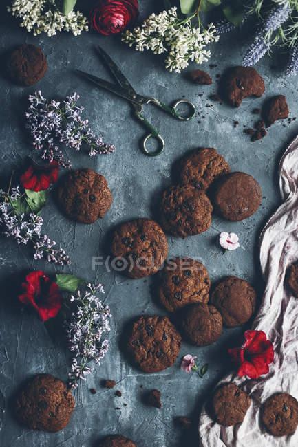 Biscuits aux pépites de chocolat cuits au four sur une surface grise minable avec fleur et ciseaux — Photo de stock