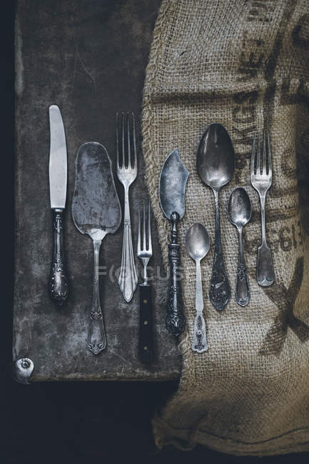 Vintage silver kitchen cutlery on sackcloth on shabby rustic table — Stock Photo